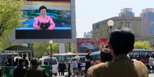 North Koreans watch as their country's most famous newscaster announces leader Kim Jong Un's proposal to suspend nuclear tests and long-range missile launches on a giant screen on Pyongyang's newly built Mirae Scientists' Street Saturday, April 21, 2018. Kim is to hold a summit with South Korea's president next week and with U.S. President Donald Trump in late May or June. (AP Photo/Cha Song Ho)