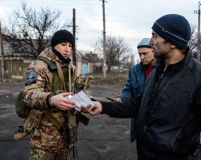 Un membre du régiment de police Dnipro 1 contrôle les passants durant une patrouille dans la rue Lénine, à Marinka (Ukraine), le 22 février.