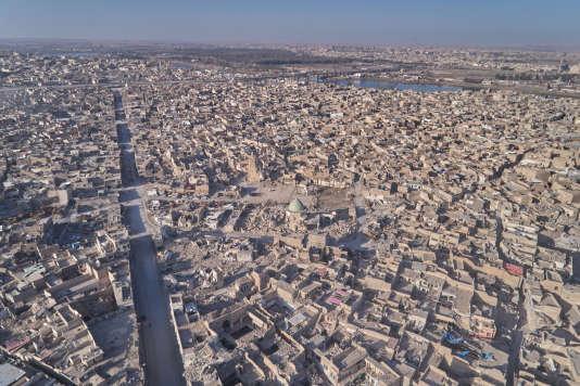 A Mossoul (Irak), vue générale des destructions autour de l'artère centrale rectiligne, une faille dans le centre historique. De chaque côté, entrelacs de venelles et maisons à cour centrale serrées les unes aux autres, certaines en bon état.
