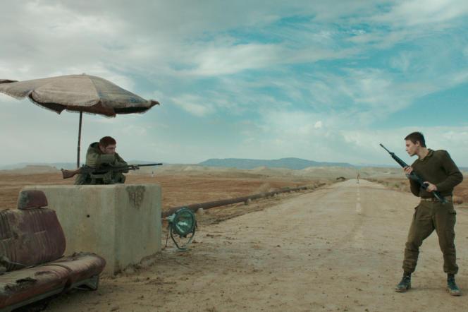 Dans un désert boueux, le point de passage gardé par des soldats israéliens est bordé d'une casemate protégée par un parasol en lambeaux. Avec àgauche, Yonatan Shiray, et àdroite, Itay Exlroad, dans« Foxtrot», de Samuel Maoz.