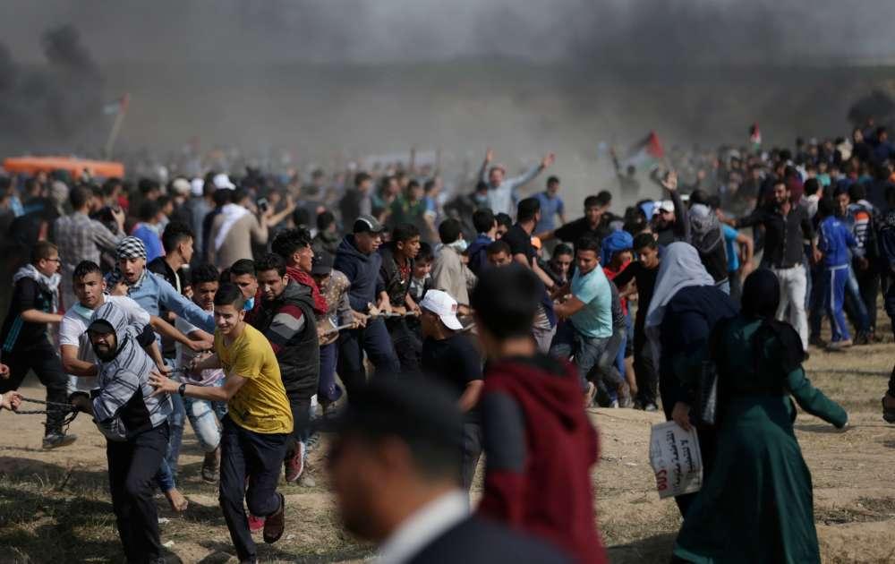 Des manifestants palestiniens tentent d'abattre une partie de la clôture de la frontière entre Israël et Gaza, à l'est de la ville de Gaza.
