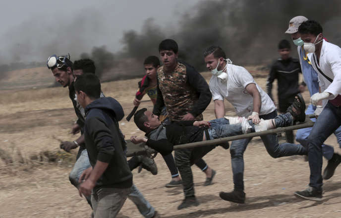 Un manifestant palestinien blessé aux jambes est éloigné des heurts à la frontière israélienne avec Gaza, le 20 avril.