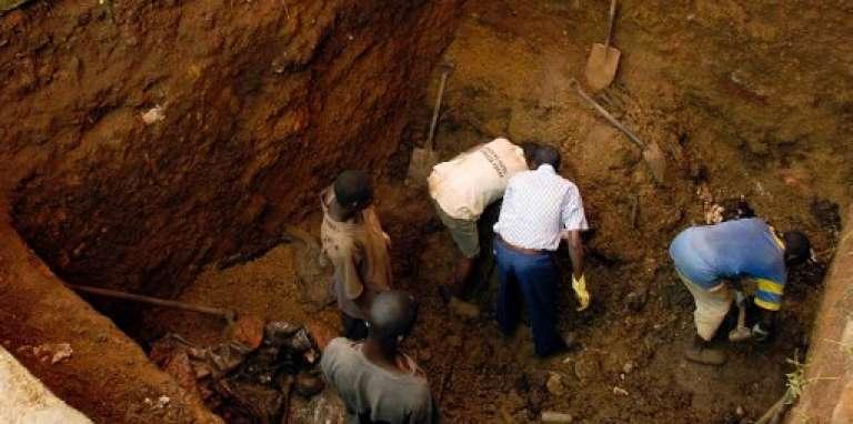 Des habitants de quartier de Nyamirambo, à Kigali, excavent une fosse commune datant de 1994, le 5avril 2004.