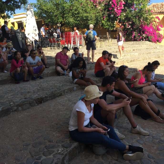 Un groupe de touristes à la recherche de réseau sur les marches de la cathédrale de Trinidad, l'un des rares endroits où il est possible de se connecter.