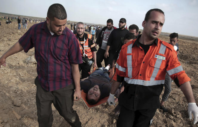 Des infirmiers palestiniens évacuent un manifestant blessé, à la frontière israélienne avec Gaza, le 27 avril.