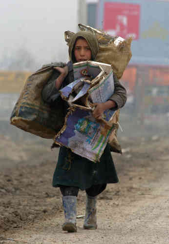 Photo prise le 5 février 2007 : une jeune Afghane de 9 ans, Fatema, transporte des ordures pour les récycler dans les rues de Kaboul.