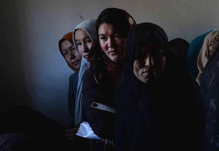 Photo prise le 30 mars 2014 : des Afghanes font la queue pour recevoir leur carte d'électrice, à Kaboul, quelques mois avant l'élection présidentielle.