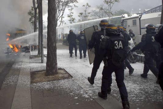 Intervention des forces de l'ordre pour éteindre une voiture incendiée lors des débordements en marge du défilé syndical, à Paris, le 1er mai.
