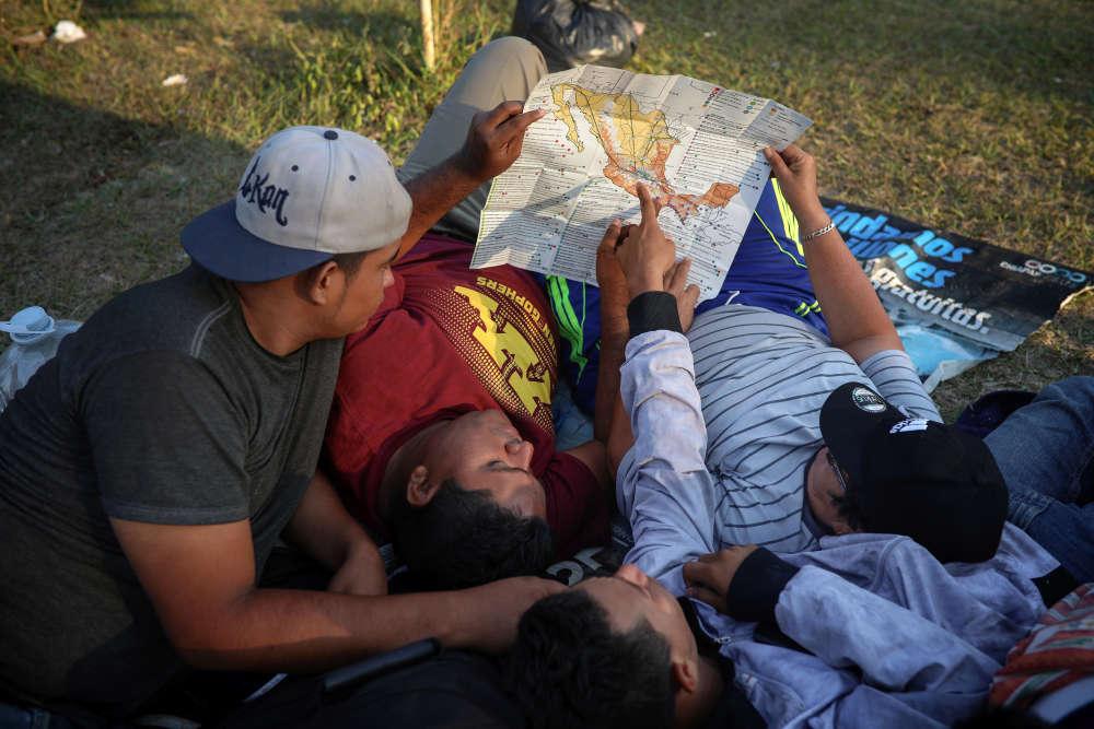 Des hommes étudient une carte du Mexique dans l'Etatde Oaxaca, au Mexique, le 4 avril.Après des jours de marche le long des routes et des voies ferrées, les organisateurs prévoient maintenant d'essayer d'obtenir des bus pour continuer la route.