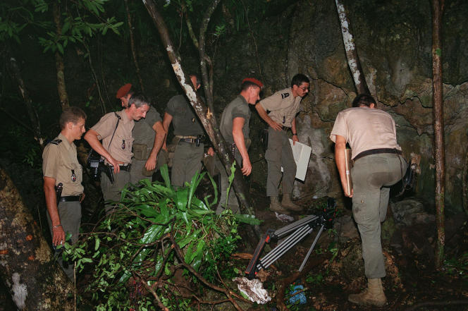 Des militaires français inspectent, le 6 mai 1988 à Ouvéa, l'entrée de la grotte de Gossanah.