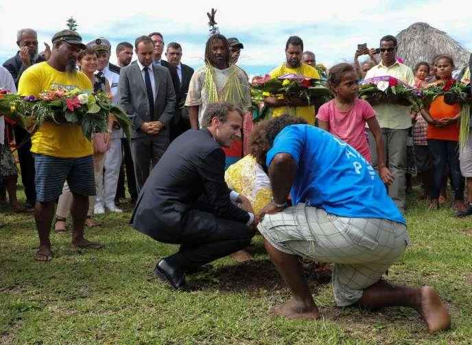 Le président Emmanuel Macron plante un cocotier sur l'île d'Ouvéa, le 5 mai 2018.