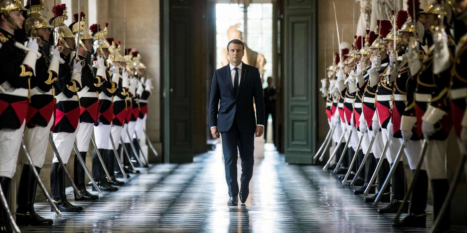 (FILES) In this file photo taken on July 3, 2017 French President Emmanuel Macron walks through the Galerie des Bustes (Busts Gallery) to access the Versailles Palace's hemicycle for a special congress gathering both houses of parliament (National Assembly and Senate) in the palace of Versailles, outside Paris. A year after his march to power, French President Emmanuel Macron's reformist zeal has endeared him to part of the electorate but polls show him as still unloved by most of the country. Macron suffered a sharp drop in popularity when he began to push through changes to labour law last September that make hiring and firing easier. / AFP / POOL / Etienne LAURENT