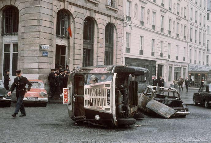 Un policier inspecte le 25mai 1968 une voiture de police renversée et une autre incendiée lors des échauffourées qui ont opposé des étudiants aux forces de l'ordre dans la nuit, au quartier Latin à Paris.