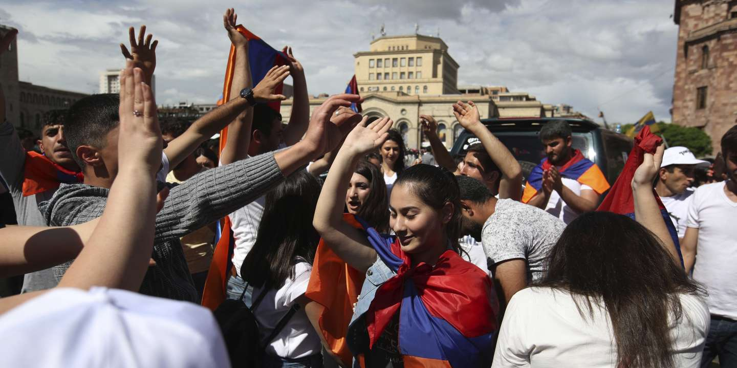 People dance at the Republic Square in Yerevan, Tuesday, May 8, 2018. Tens of thousands of supporters of Nikol Pashinian are celebrating on the central square of Armenia's capital after the protest leader was elected the country's prime minister. (AP Photo/Thanassis Stavrakis)