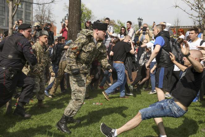 Des individus en treillis militaire s'en prennent violemment à des manifestants anti-Poutine, place Pouchkine, à Moscou, le 5 mai.