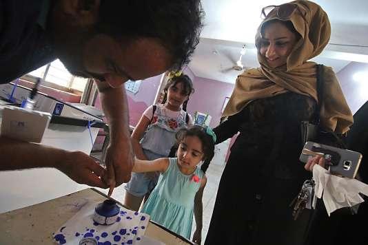 Une femme irakienne, qui vient aux élections législatives, en compagnie de sa fille, samedi 12 mai 2018.