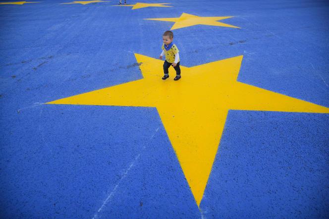 Enfant marchant dans une rue aux couleurs de l'Europe, à Bucarest (Roumanie), le 12 mai.