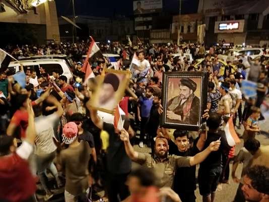 Des partisans du chef religieux chiite Moqtada Al-Sadr (en portrait encadré), à Bagdad, après l'annonce des résultats des législatives, le 14 mai2018.