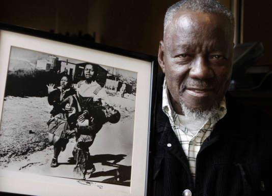 27avril 2011, le photographeSam Nzima pose devant sa photographie montrant un jeune écolier noir, mortellement blessé par la police de l'apartheid durant le soulèvement de Soweto en 1976.