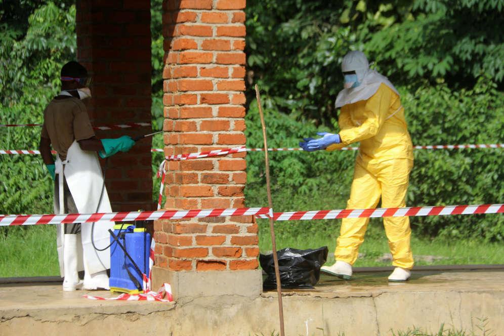 Un agent de santé est aspergé de chlore, le 12 mai, après avoir visité le service d'isolement de l'hôpital de Bikoro, qui avait alors reçu un nouveau cas suspect d'Ebola.