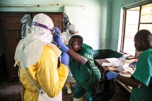 Des professionnels de la santé s'équipent avant de soigner des patients qui seraient contaminés par Ebola, à l'hôpital de Bikoro, en RDC, le 12 mai.