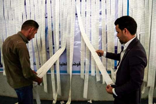 Des employés de la Commission électorale examinent l'impression des résultats provenant des machines à voter, à Najaf, le 13 mai.