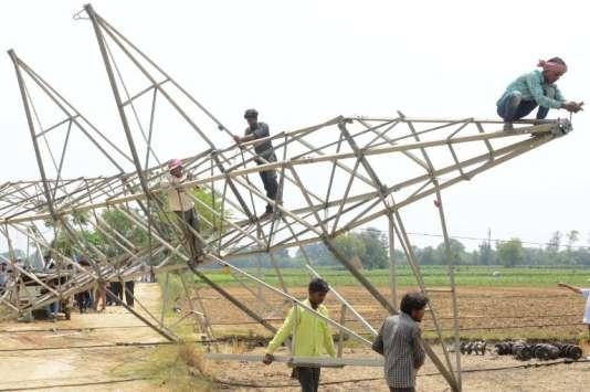 Des travailleurs enlèvent un pylône électrique tombé à terre dans la tempête du 12mai, près de la ville d'Amritsar, dans l'Etat duPendjab (dans le nord du pays).