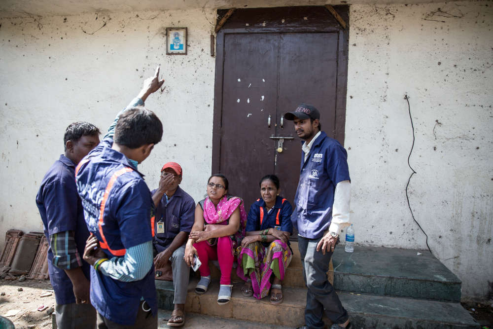 Après leur tournée matinale, les collecteurs de déchets de SWaCH discutent avec Hema Bhalerao la responsable de la coopérative dans le quartier.