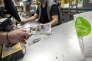 Un client paie ses courses dans un magasin de produits bio de Montreuil (Seine-Saint-Denis) en utilisant la « pêche », la monnaie locale, le 11 mai.