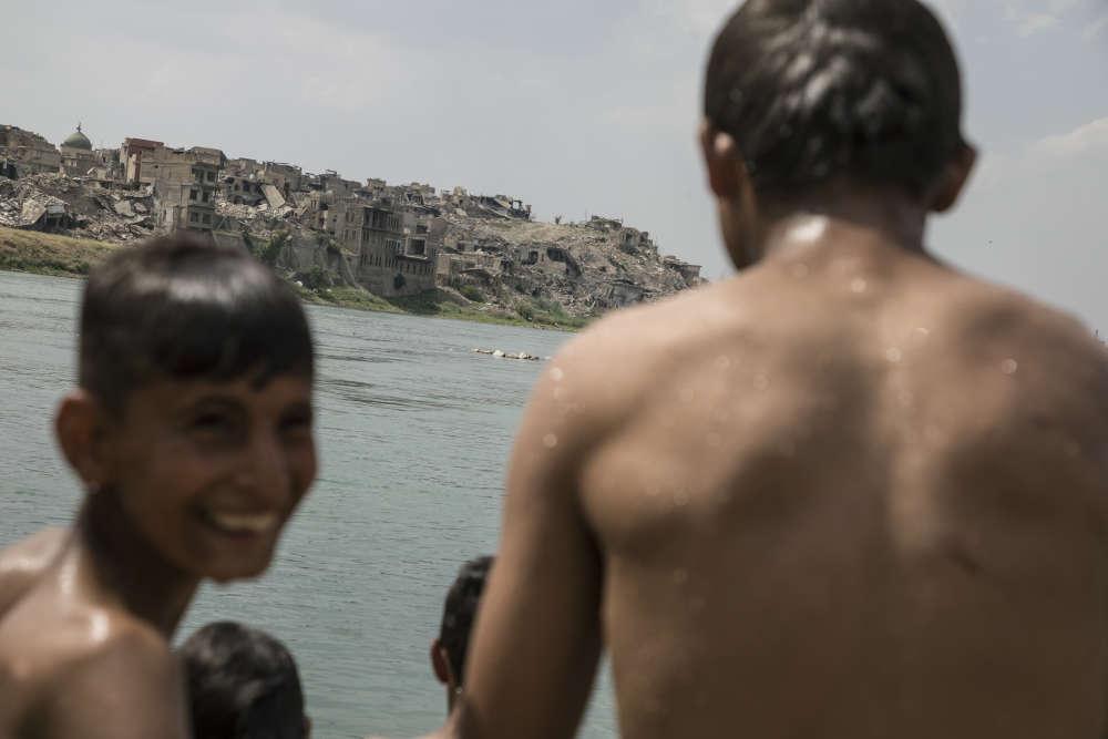La partie de la vieille ville détruite au cours des dernières batailles de juillet 2017 vue depuis la rive du Tigre, où les jeunes viennent maintenant se baigner librement.