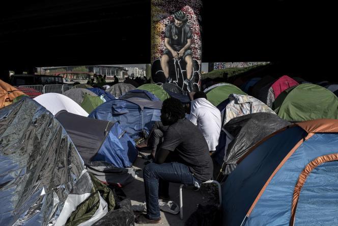Des migrants à l'extérieur de leurs tentes sous un pont, porte de La Villette, à Paris, le 20 avril.