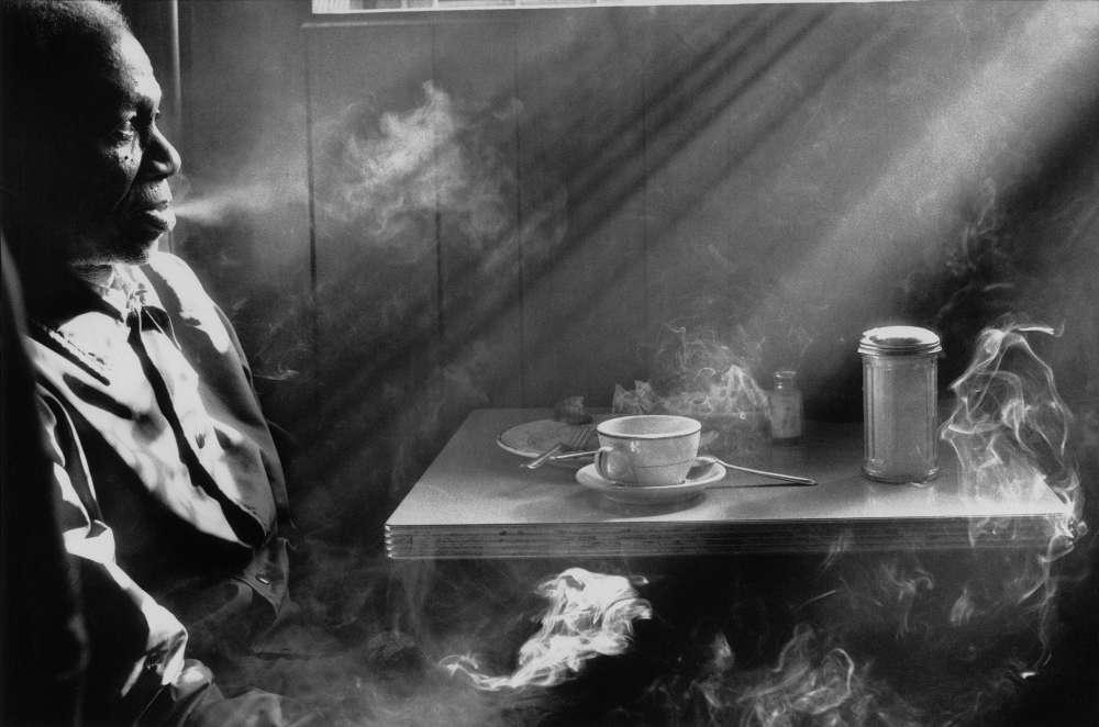 «Cette photographie a été prise dans un restaurant de la 14erue, à Manhattan. Une scène ordinaire à une époque où café rimait avec cigarette, mais une scène magnifiée par cette lumière douce et pénétrante qu'Harold Feinstein a su capter avec brio.»