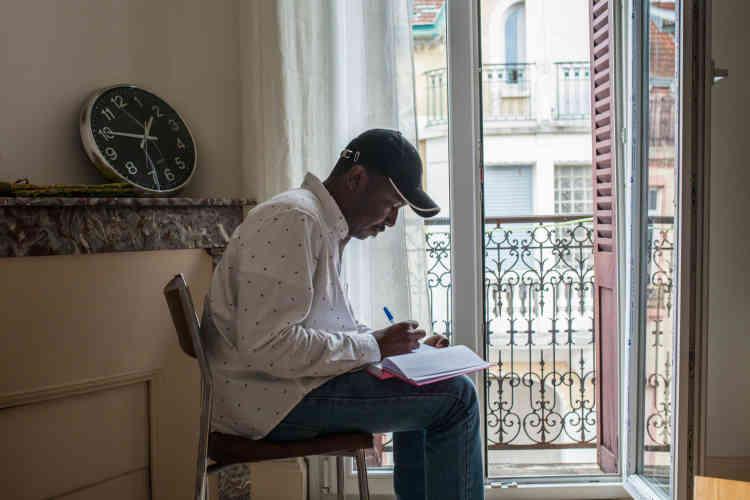 Ali tient un journal intime dans lequel il consigne des réflexions sur son pays d'origine, le Soudan, et sur sa vie en France. Ici, dans son appartement.