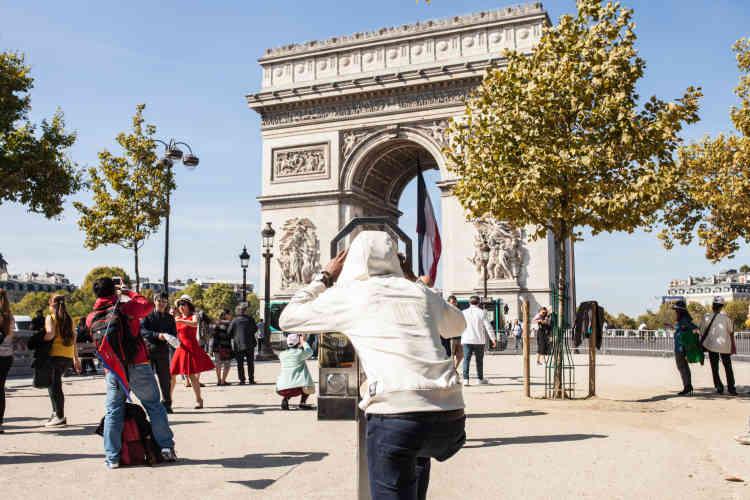 Sur l'avenue des Champs Elysées, Hassan observe l'Arc de triomphe, le lendemain du concert que les Soudan Célestins Music ont donné au Festival Culture au quai.