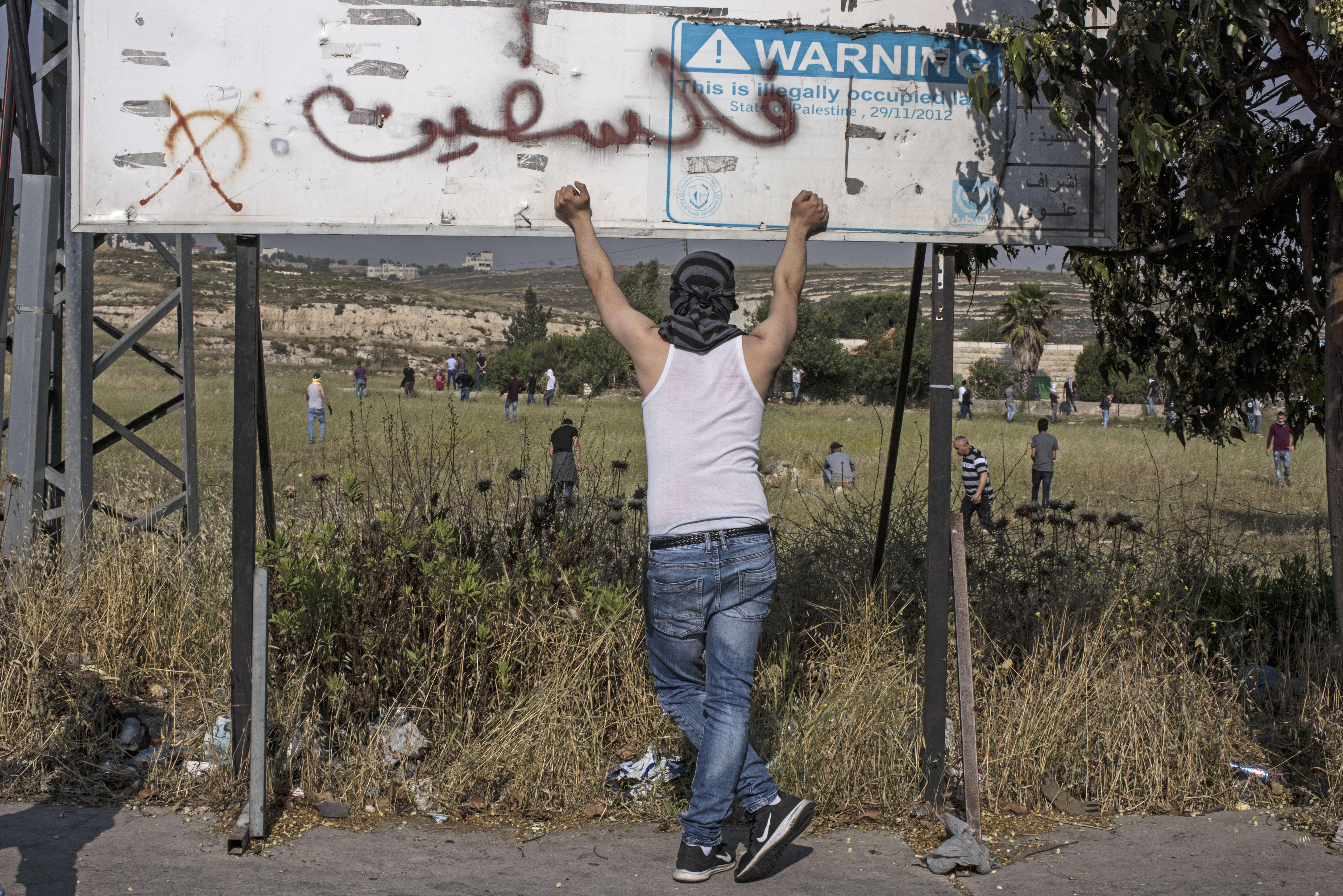 Un manifestant palestinien se protège derrière un panneau sur lequel quelqu'un a ajouté un autocollant : « Attention, le terrain est occupé. »