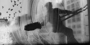 """«Harold Feinstein aimait ses accidents heureux qui font les belles photographies. Celle-ci en est un bel exemple. Alors qu'il entre dans un bâtiment de bureaux à Manhattan pour un rendez-vous, il saisit cet """"instant décisif""""»."""