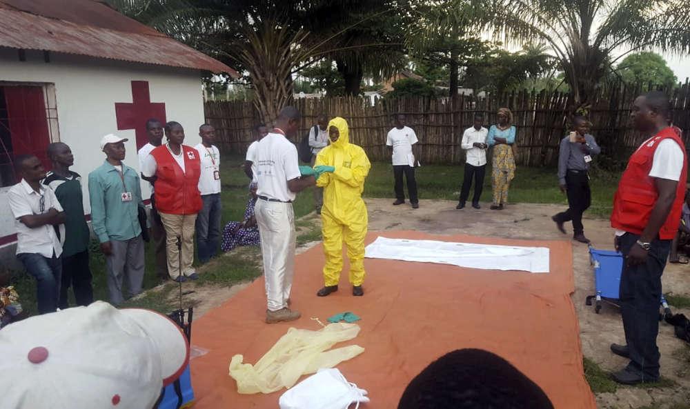 Des membres d'une équipe de la Croix-Rouge portent des vêtements de protection avant de traiter des personnes soupçonnées d'être touchées par Ebola, le 14 mai.