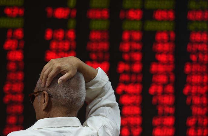Un investisseur observe les mouvements des cours des actions à Pékin, en juin 2016.