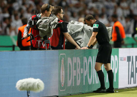Un arbitre allemand vérifiant une action sur l'écran en bord de terrain, lors d'un match de Bundesliga.