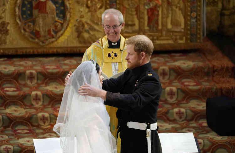 Le prince Harry enlève le voile de la robe de Meghan Markle lors de leur cérémonie de mariage.