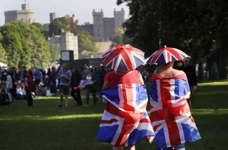 Enveloppés dans leur«UnionJack», des sympathisants marchent vers la chapelle Saint-Georges, là où le couple princier va se marier, et qu'on peut apercevoir en arrière-plan, alors que le soleil se lève sur la Grande-Bretagne.