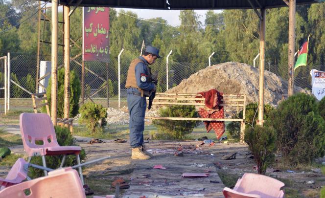 Un policier inspecte les abords du stade visé vendredi soir par des explosions à Jalalabad, en Afghanistan, le samedi 19 mai 2018. Au moins huit personnes ont été tuées et 45 blessées, ont rapporté samedi les autorités.
