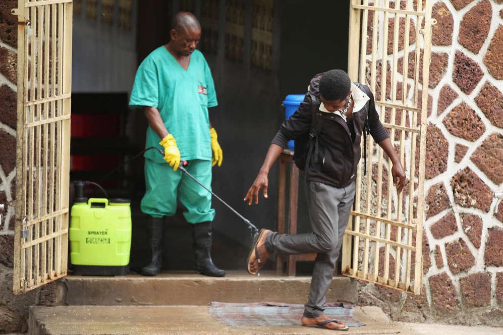 Depuis que de nouveaux cas ont été détectés, des mesures ont été prises pour éviter que le virus ne se propage.Un agent de santé pulvérise, le 20 mai, du chlore sur un visiteur après avoir quitté l'établissement d'isolement, prêt à recevoir des cas suspects d'Ebola, à l'hôpital général de Mbandaka.