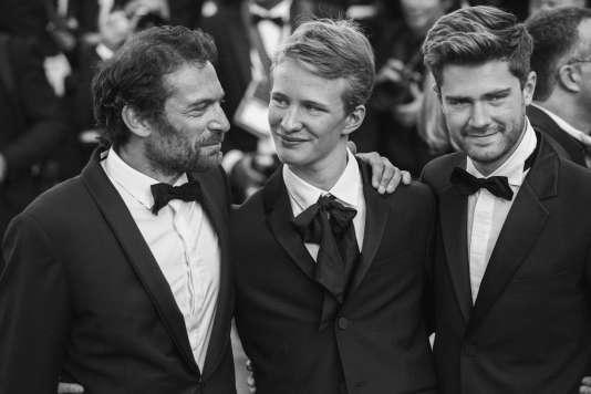 De gauche à droite : les acteurs belges Arieh Worthalter et Victor Polster, le réalisateur belge Lukas Dhont lors de la montée des marches pour la cérémonie de clôture au 71e Festival de Cannes, le 19 mai 2018.
