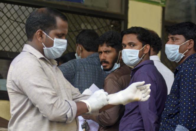 A Kozhikode, dans l'Etat du Kerala, lundi 21 mai 2018, des patients attendent à l'extérieur d'un hôpital, portant un masque par mesure de précaution.