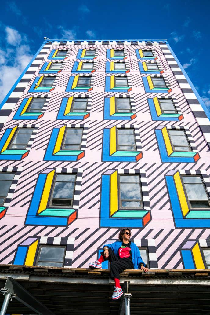 L'artiste de street-art Camille Walala devant la façade de 40 mètres de haut qu'elle a peinte à Brooklyn, à l'initiative du festival WantedDesign.