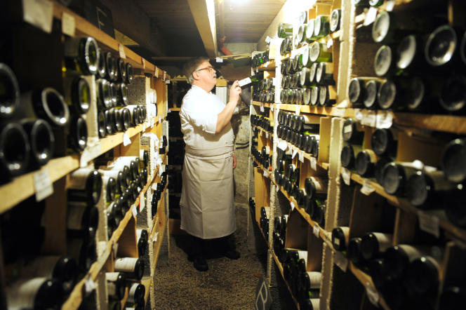 Le chef du restaurant L'Auberge bretonne sélectionne une bouteille de vin de sa cave à vins, à La Roche-Bernard (Morbihan), le9 mars 2010.