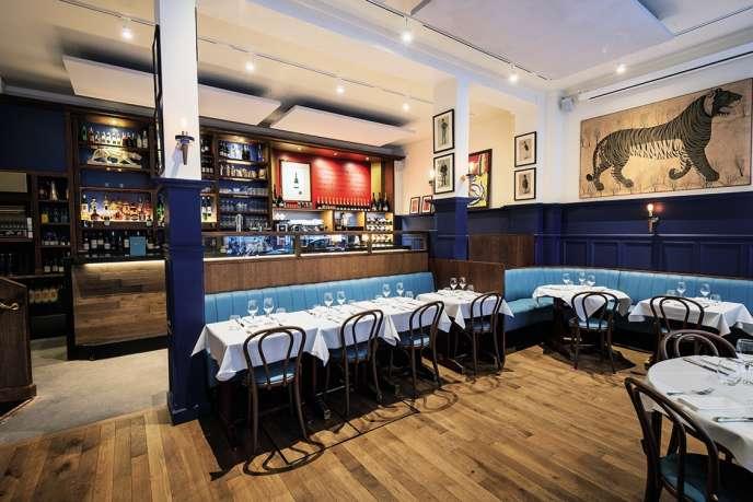 Le restaurant L'Entente dans un décor aux vastes banquettes, nappes blanches et chaises Thonet.