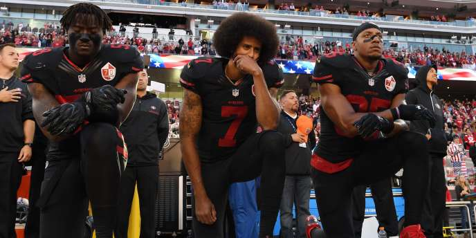 Le 6 octobre 2016 Eli Harold, à gauche, Colin Kaepernick, au centre,et Eric Reid à droite, joueurs des San Francisco 49ers s'agenouillent en signe de protestation, avant le début d'un match de contre les Arizona Cardinals, au stade de Santa Clara, en Californie.