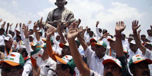Legislators of Indian National Congress and Janata Dal (Secular) alliance raise their hands as they sit next to a statue of Mahatma Gandhi in protest against the swearing-in of Bharatiya Janata Party (BJP) leader B. S. Yeddyurappa as Chief Minister of Karnataka state in Bangalore, India, Thursday, May 17, 2018. Indian Prime Minister Narendra Modi's Hindu nationalist party ended Congress party rule in a key southern state on Thursday, but its poll victory was marred by questions over who has the right to form the government. (AP Photo/Aijaz Rahi)